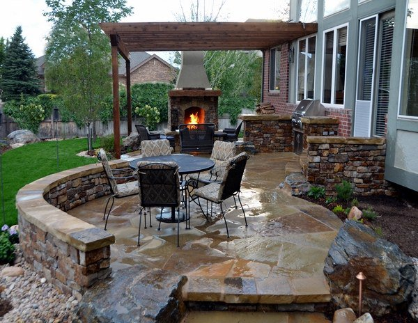 Outdoor kitchen on flagstone patio and wooden pergola